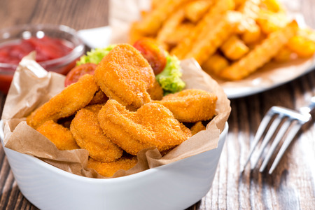 Portion of golden Chicken Nuggets with some french fries Stock Photo