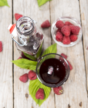 treacle: Raspberry Treacle in a glass on vintage weathered wooden background Stock Photo