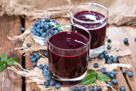 Fresh made Blueberry Juice with some fruits on wooden background