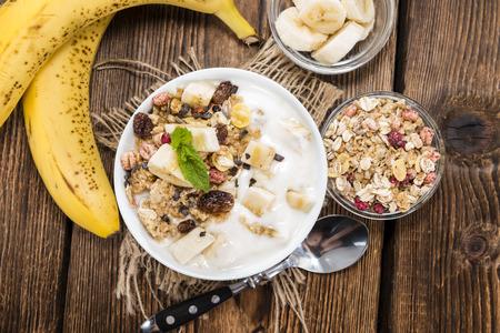 yogurt natural: Porción de yogurt de plátano en un recipiente con miel y muesli