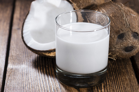 verre de lait: Lait de coco dans un verre sur fond de bois fonc� (gros plan)