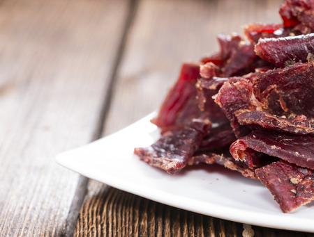 Portion of Beef Jerky (close-up shot) on vintage wooden background Stock Photo