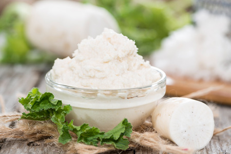 Horseradish Sauce in a small bowl on wooden background (close-up shot)