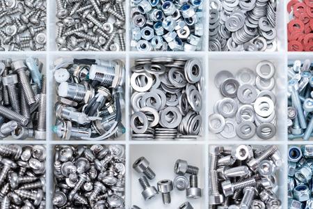 pernos: Diferentes tornillos y otras piezas clasificadas en una caja (cerca de disparo)