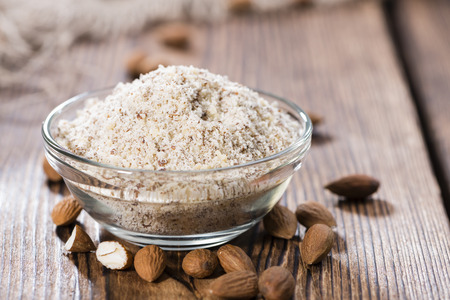 Heap of grated Almonds (close-up shot) on wooden background Stock Photo