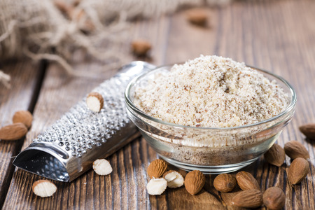 Portion of fresh grated Almonds on wooden background