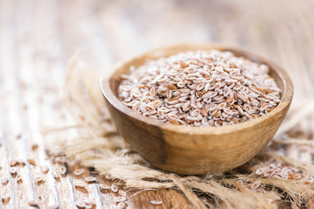 Psyllium Seeds in a bowl (close-up shot) on wooden background