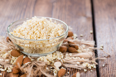 Small bowl with Minced Almonds (close-up shot) on rustic wooden background