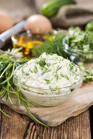 close uo: Homemade Remoulade on wooden background with fresh herbs (close-uo shot)