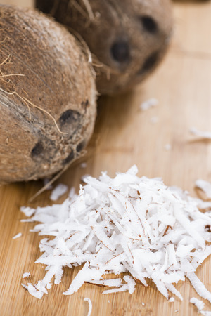 Fresh Grated Coconut (detailed close-up shot) on wooden background photo