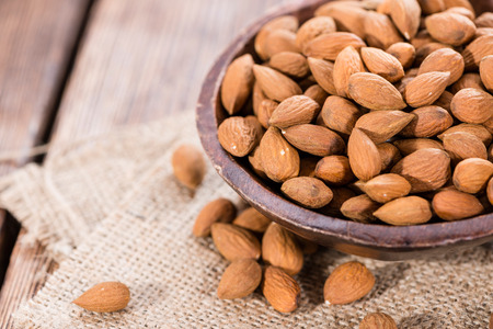 Portion of dried Almonds (close-up shot) on wooden background Stock Photo