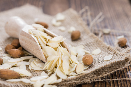 Portion of Almond Flakes on wooden background