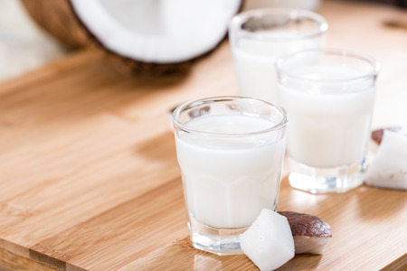 Shot Glass with Coconut Liqueur on wooden background photo