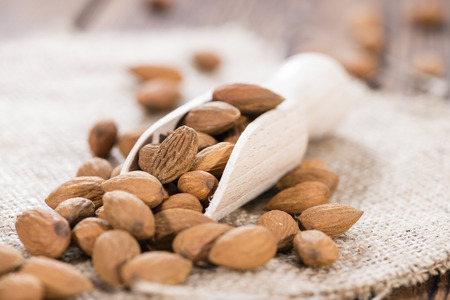 Portion of Almonds on a Wooden Spoon (close-up shot)