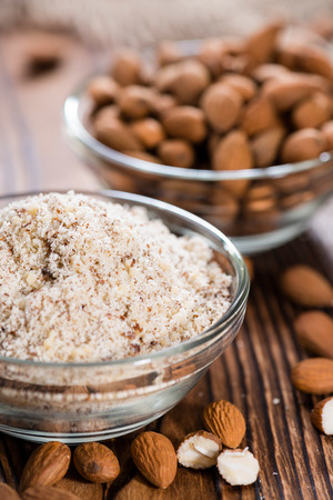 Portion of grated Almonds (detailed close-up shot on wooden background)