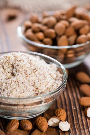 mandel: Portion of grated Almonds (detailed close-up shot on wooden background)