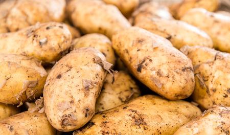 Portion of fresh Potatoes on vintage background photo