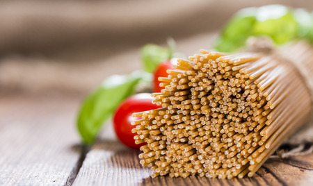 Portion of wholemeal Spaghetti (close-up shot) on vintage wooden background photo