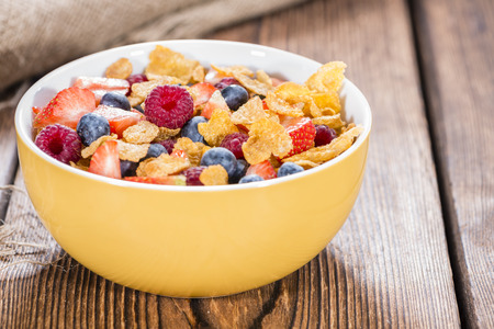 Fresh made Breakfast (Cornflakes with different Berries) on wooden background photo