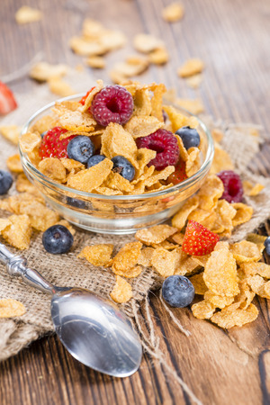 Cornflakes with fresh Strawberries, Raspberries and Blueberries on wooden background photo