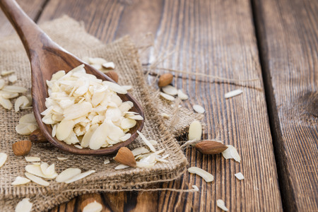 Portion of Almond Flakes on wooden background photo