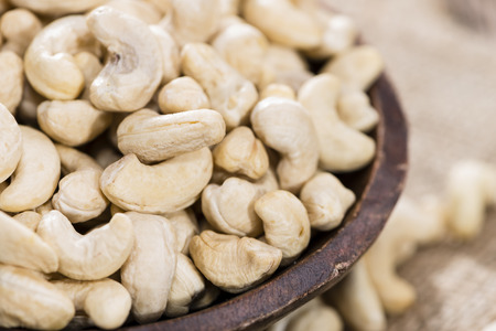 Heap of dried Cashew Nuts (close-up shot) on rustic background photo