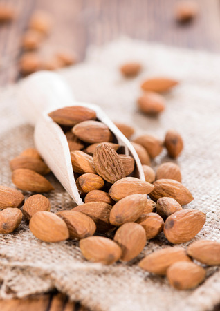 Almonds (detailed close-up shot) on wooden background