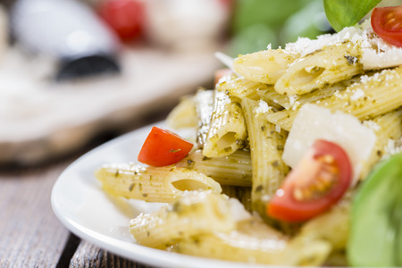 Fresh made portion of Penne (with Basil Pesto) on wooden background photo