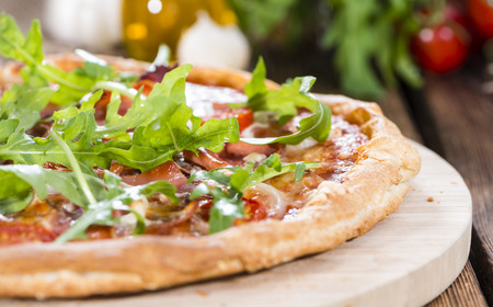 Ham Pizza with rocket and fresh tomatoes on rustic wooden background photo