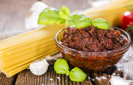 Homemade Tomato Pesto in a small bowl (on wooden background) photo