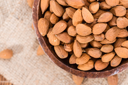 Bowl with Almonds on rustig wooden background (close-up shot) Stock Photo