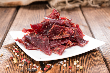 Portion of Beef Jerky on vintage wooden background Stock Photo