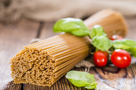 Wholemeal Spaghetti (close-up shot) on an old wooden table photo