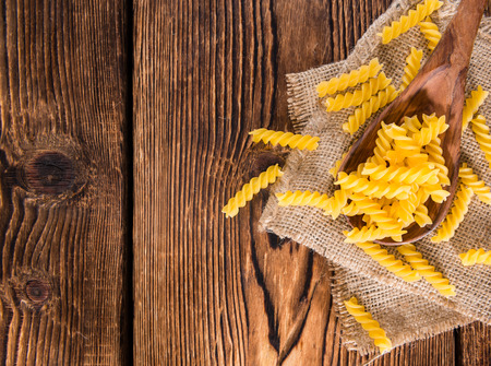 fussili: Portion of uncooked Pasta (Fussili) on rustic wooden background Stock Photo