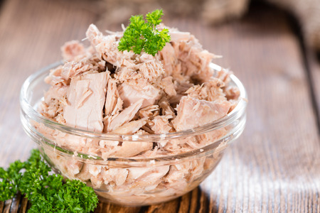 Canned tuna with fresh parsley (detailed close-up shot) on wooden background 스톡 콘텐츠