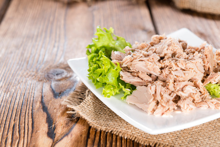 tinned: Canned tuna with fresh parsley (detailed close-up shot) on wooden background Stock Photo