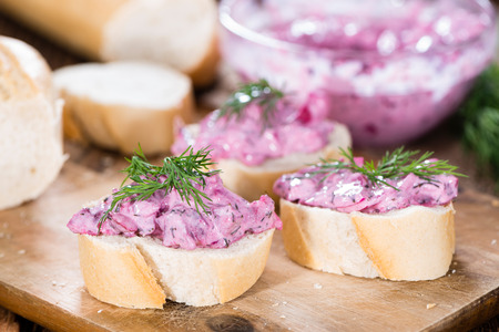 Pink Herring Salad (with beet and fresh herbs) on a piece of bread photo