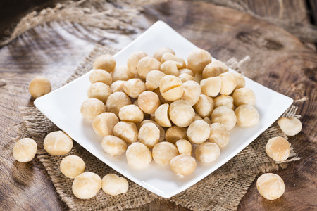 Portion of Macadamia nuts (roasted and salted) on wooden background