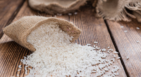 Portion of Rice on rustic wooden background (close-up shot) photo