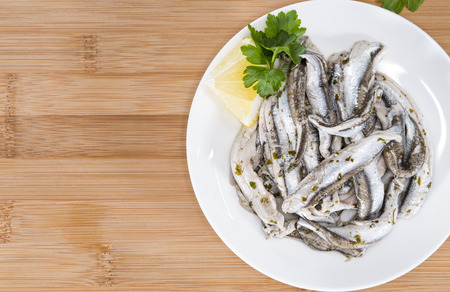 seafish: Portion of Anchovis with herbs (close-up shot)