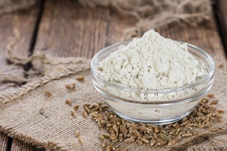 スペルト小麦の小麦粉と木製の背景に全種小鉢