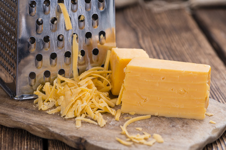 hard cheese: Grated Cheddar Cheese on rustic wooden background