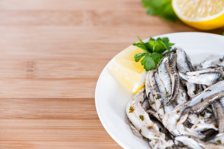 seafish: Pickled Anchovis with herbs (close-up shot) on wooden background Stock Photo