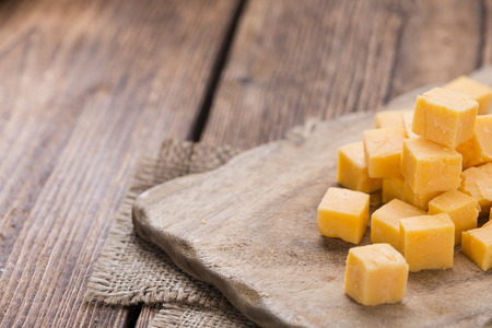 cubed: Pieces of Cheddar (close-up shot) on an old wooden table