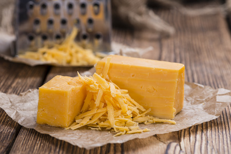 Cheddar Cheese (grated) as close-up shot on an old vintage wooden table Standard-Bild