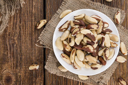 Heap of Brazil Nuts (close-up shot) on wooden background Stock Photo