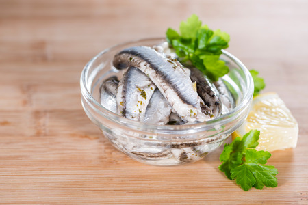 Pickled Anchovis with herbs (close-up shot) on wooden background Stock fotó