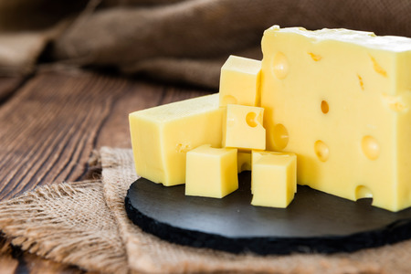 swiss cheese: Block of Cheese (close-up shot) on vintage wooden background Stock Photo