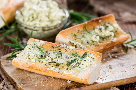 Baguette with Herb Butter and Rosemary on rustic wooden background