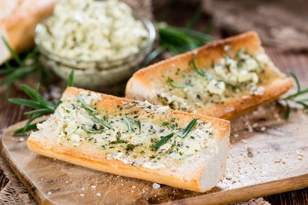 pain: Baguette avec Herb beurre et Rosemary sur fond de bois rustique